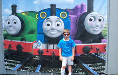 Boy in front of trains